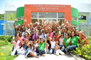 Children and staff post in front of a community technology center in Peralta Azua, Dominican Republic. Photo from the official Facebook page for Centros Tecnológicos Comunitarios.