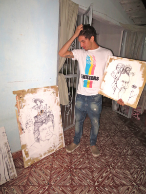 Sanabria with two of his paintings. (Photo used with permission from the VISPERA.)