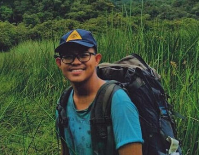 Language activist Fikri Ansori, smiling during a hiking trip. He carries a small backpack.