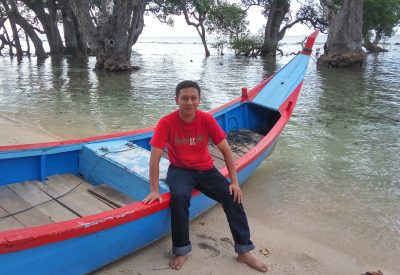 Nabil Berri, Acehnese language activist, photographed while leaning on a wooden boat by a river.