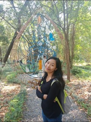 Language activist Rany Phok posing in front of a sculpture in a park.