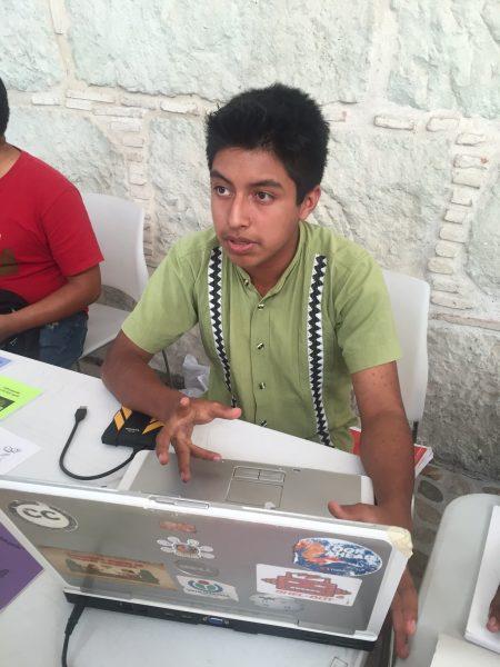 """Joaquín Yescas explicando sobre su proyecto """"Escuela del Pingüino Xhidza en la feria pública."""