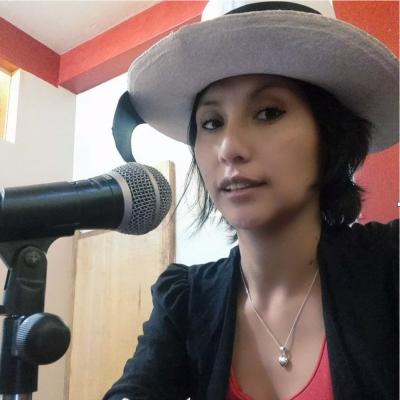 Portrait de l'activiste Liz Julissa Camacho Zuñiga, s'exprimant devant un micro