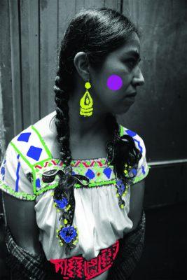 La militante linguistique Isela Xospa, les cheveux tressés, regarde hors champ. Des dessins de couleur se superposent à l'image, formant des motifs sur sa chemise.